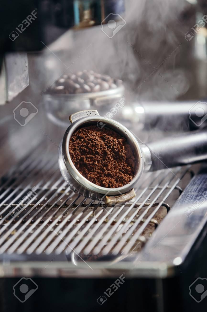 Barista roasting coffee beans grinder on coffee espresso machine - 99734824