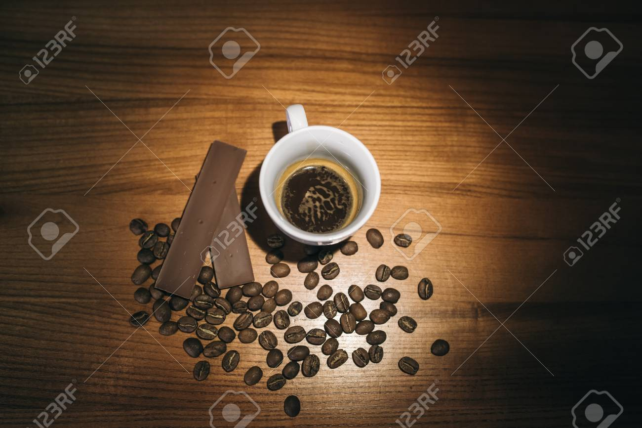 Cup of coffee with grains and chocolate on wooden table - 99836154