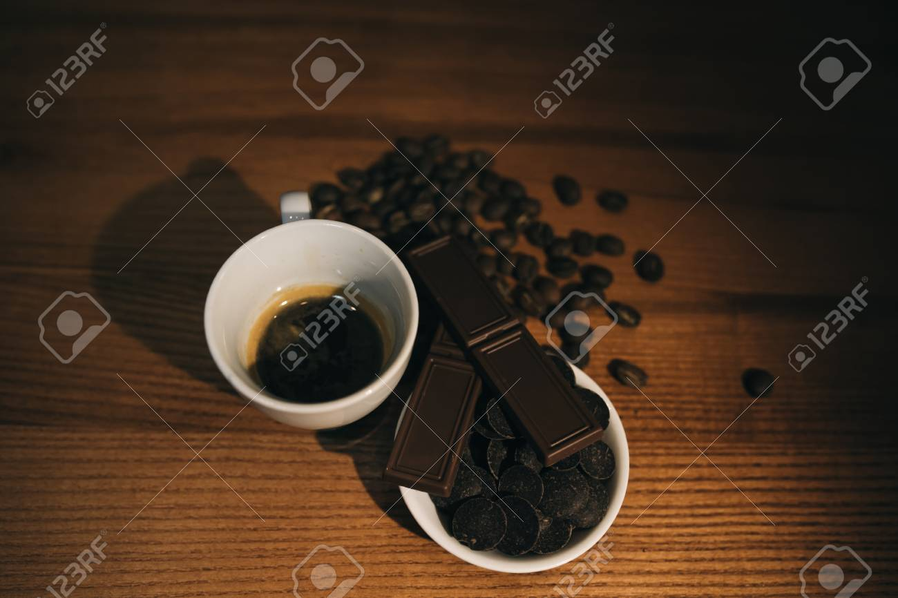 Cup of coffee with grains and chocolate on wooden table - 99856815