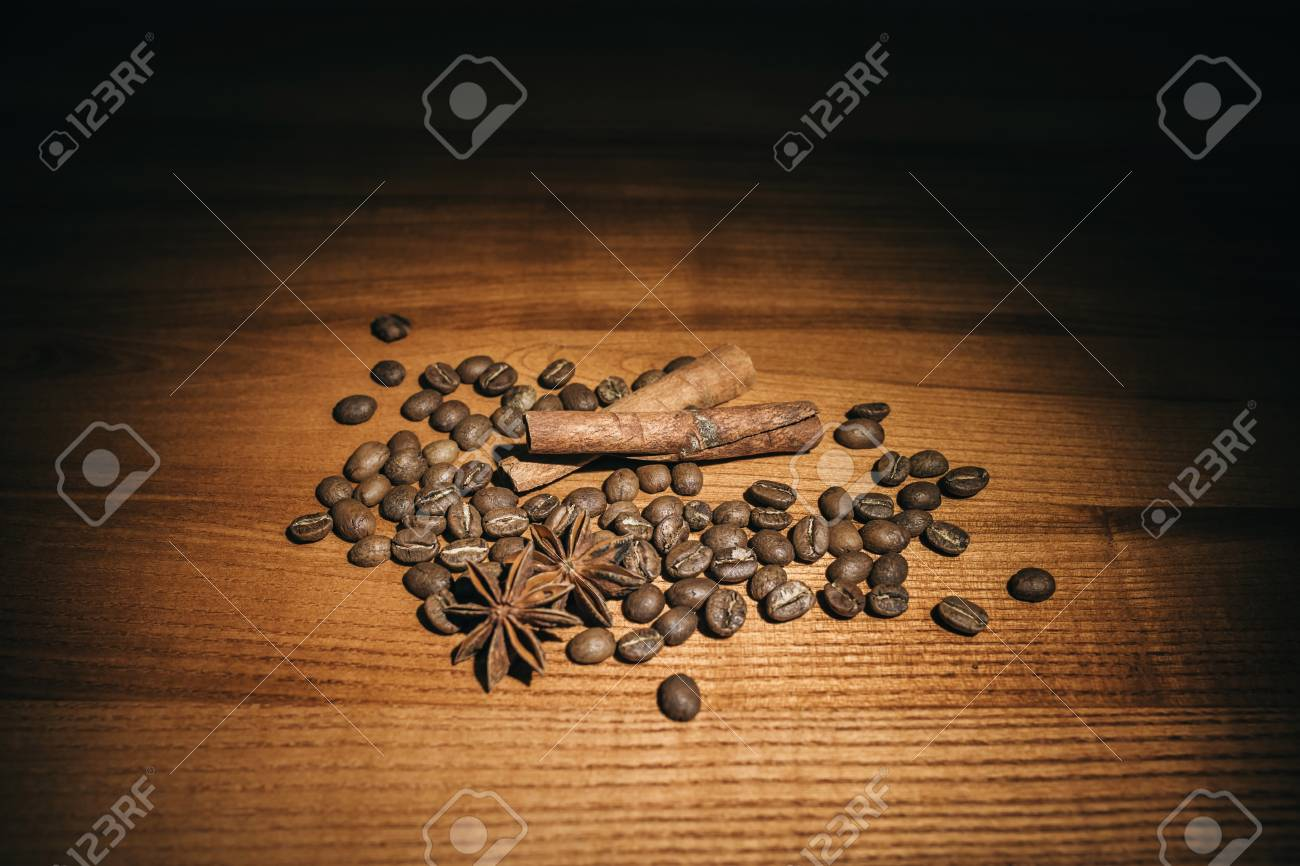 Brown background with anise, cinnamon and coffee beans. - 99832480