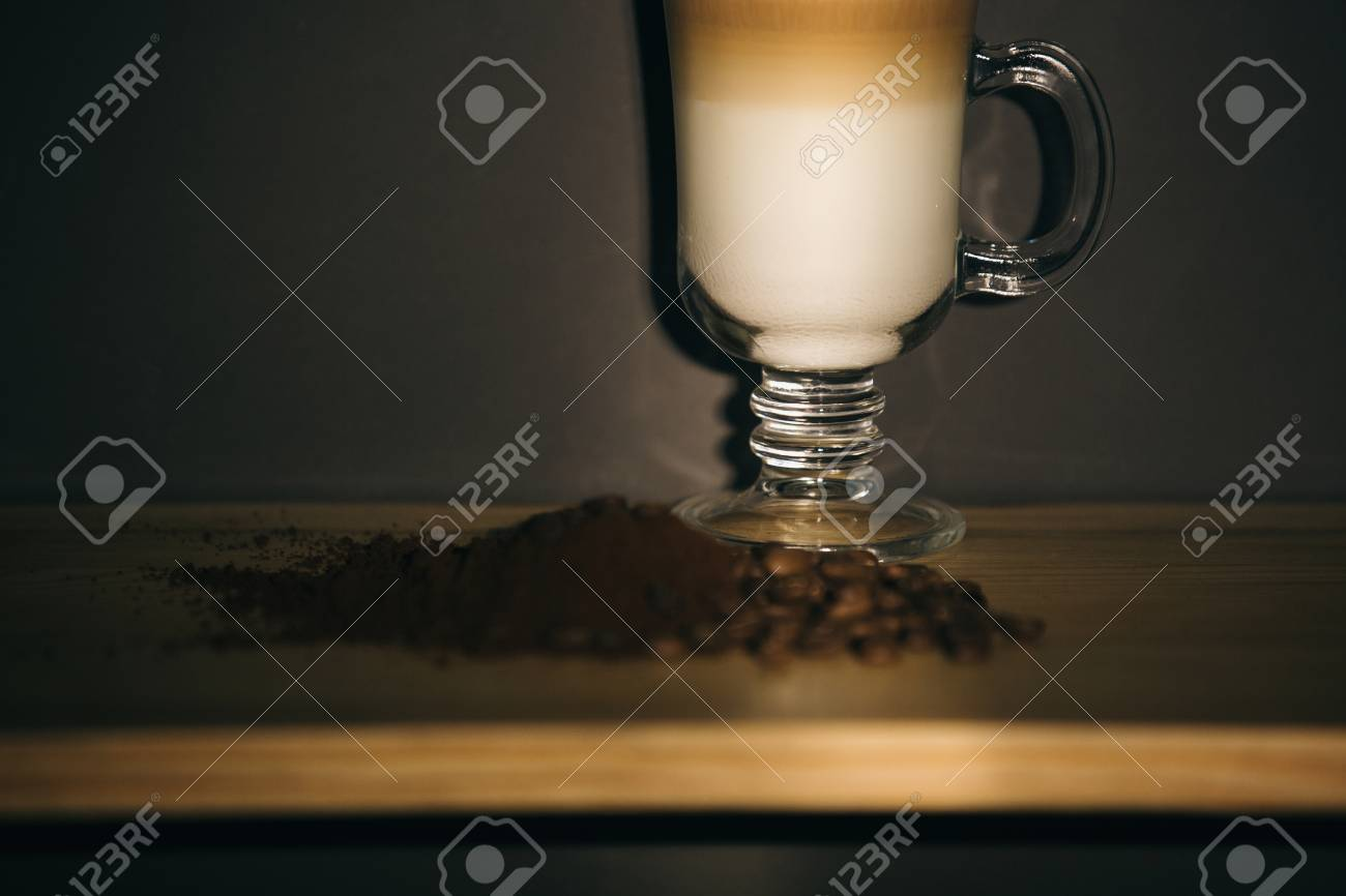 cup of latte or cappuccino coffee and brown coffee grounds - 99895896