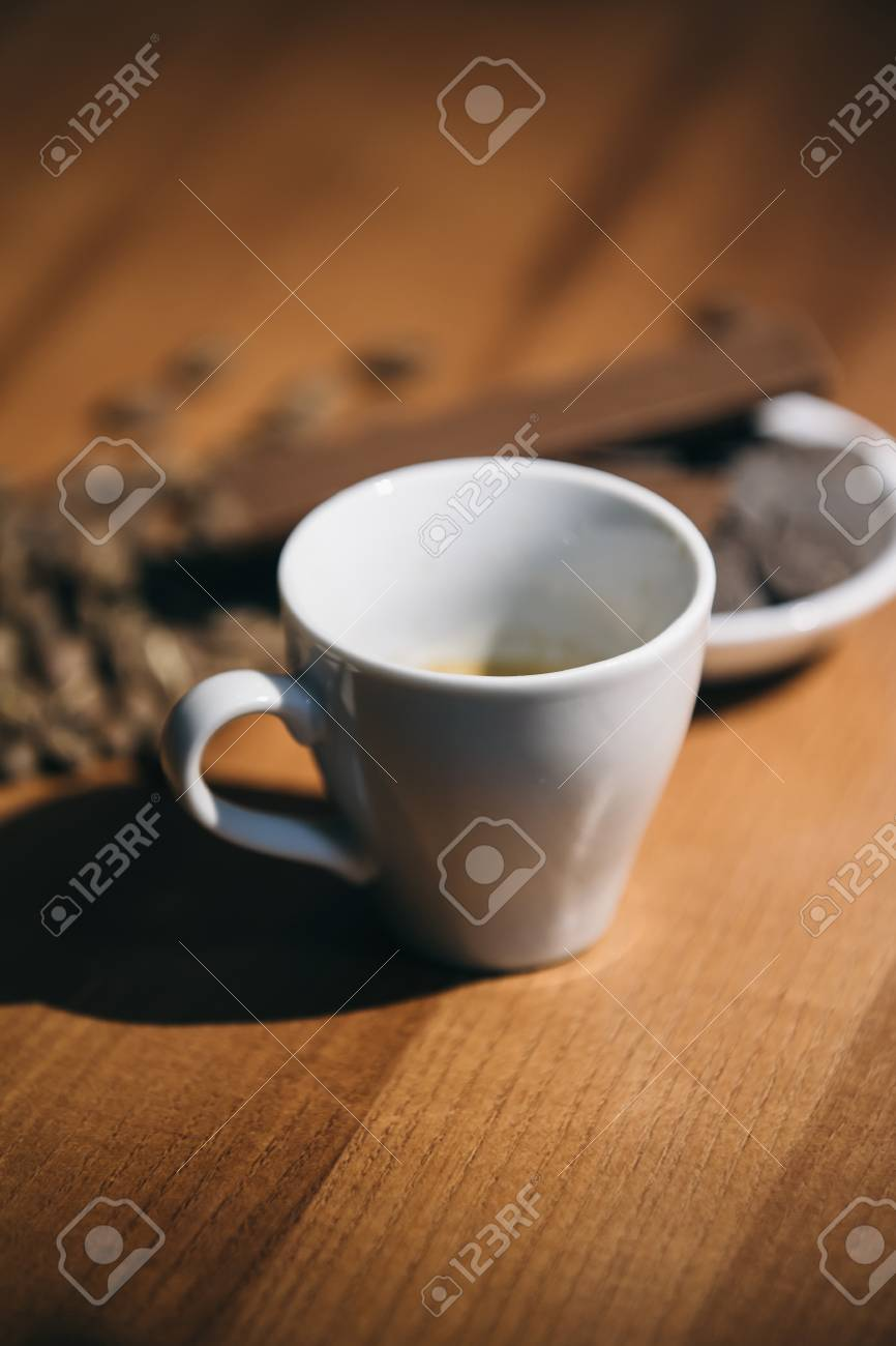 Cup of coffee with grains and chocolate on wooden table - 99869219