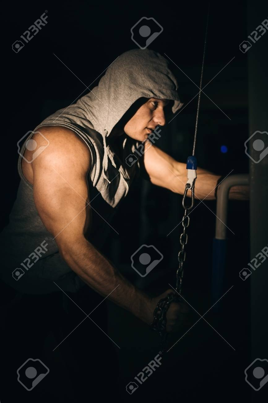 an athlete pumps his arm muscles with a chain in the gym on a dark background, - 99895928