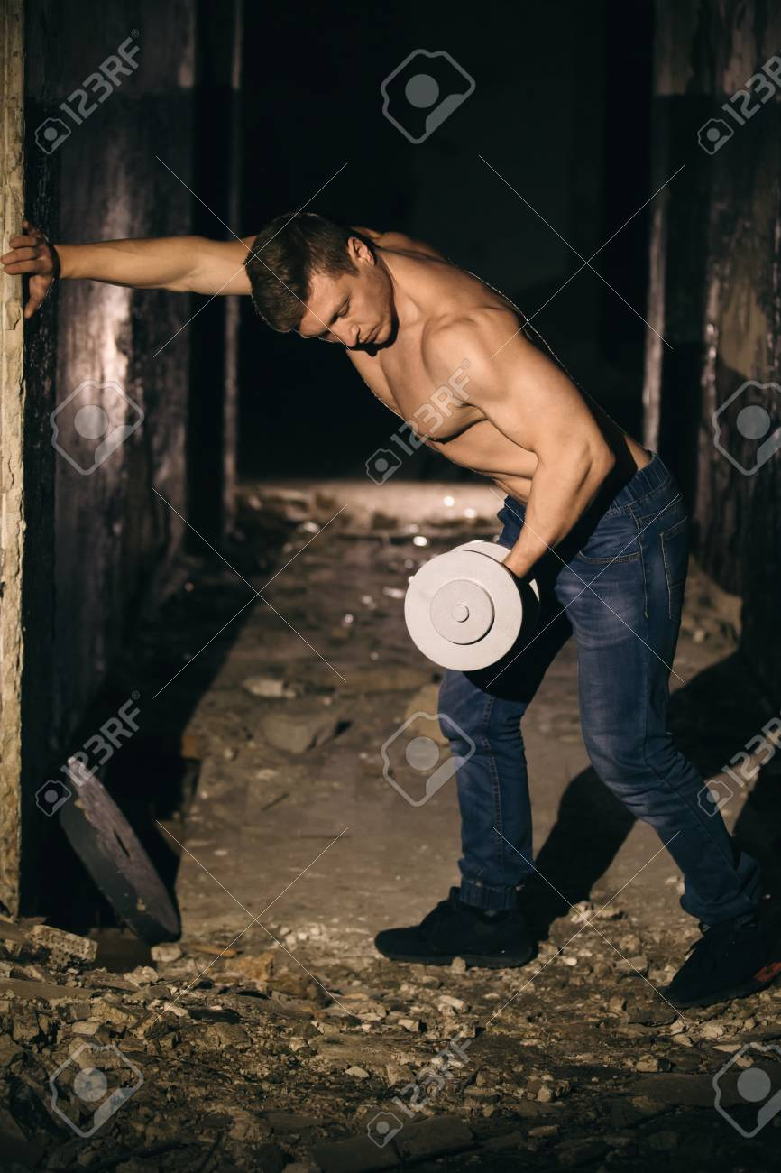 A young guy goes in for sports in a dark, shattered room under searchlights - 99977200