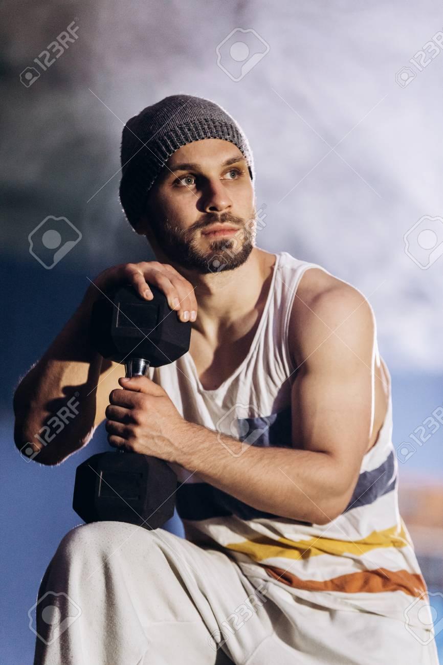 Muscular bodybuilder with dumbbells in smoke - 100922885