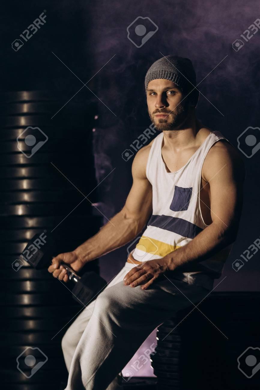 Muscular bodybuilder with dumbbells in smoke - 100902865
