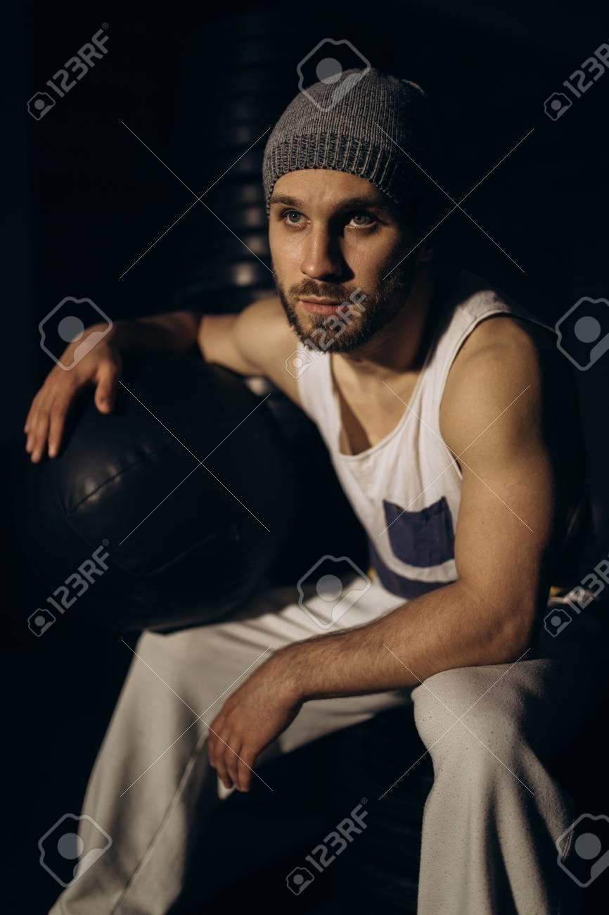 Muscular bodybuilder with dumbbells in smoke - 100944598