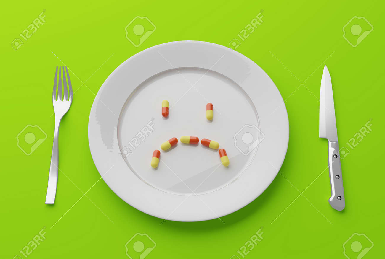pills on an empty plate with knife and fork - 158085694