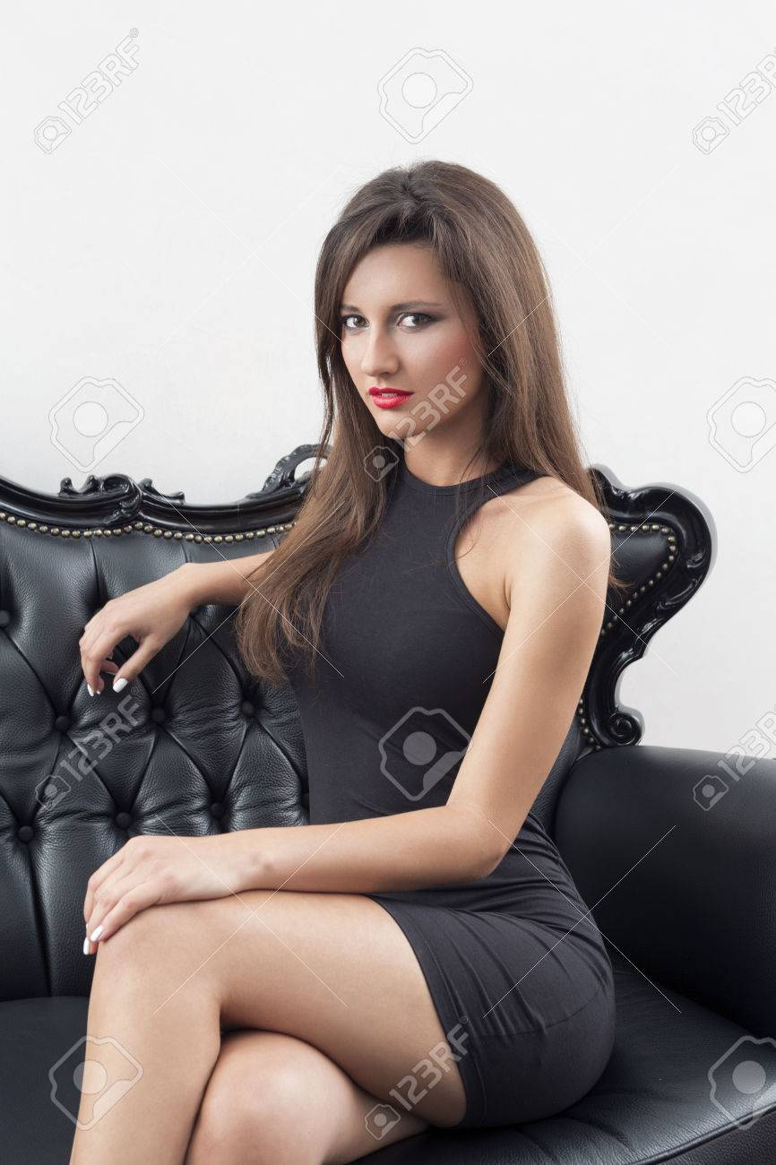 Elegant Woman In Black Dress Sitting On Black Sofa Stock Photo