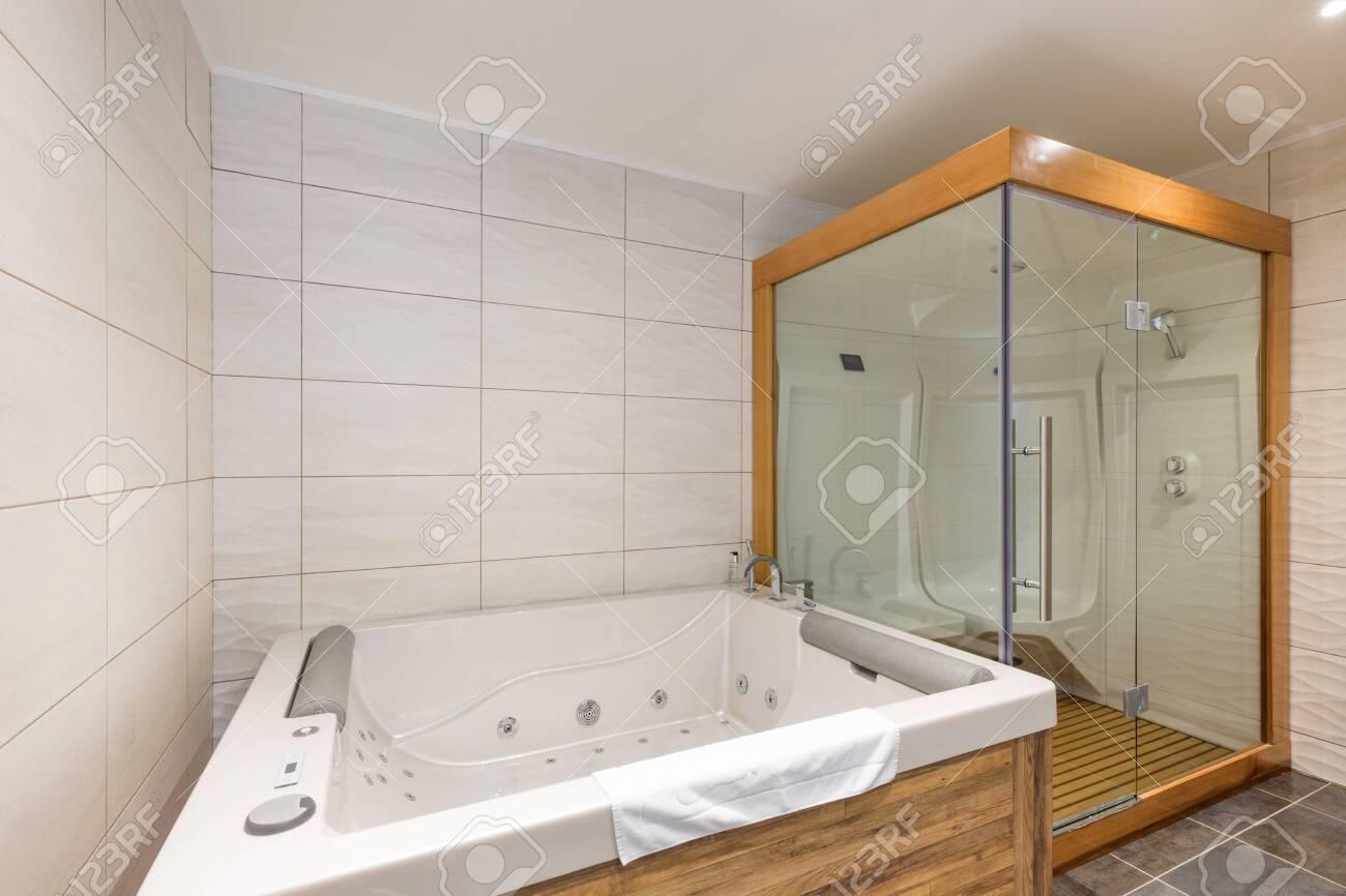 interior of luxury hotel bathroom with hydromassage bathtub and shower cabin - 154301932