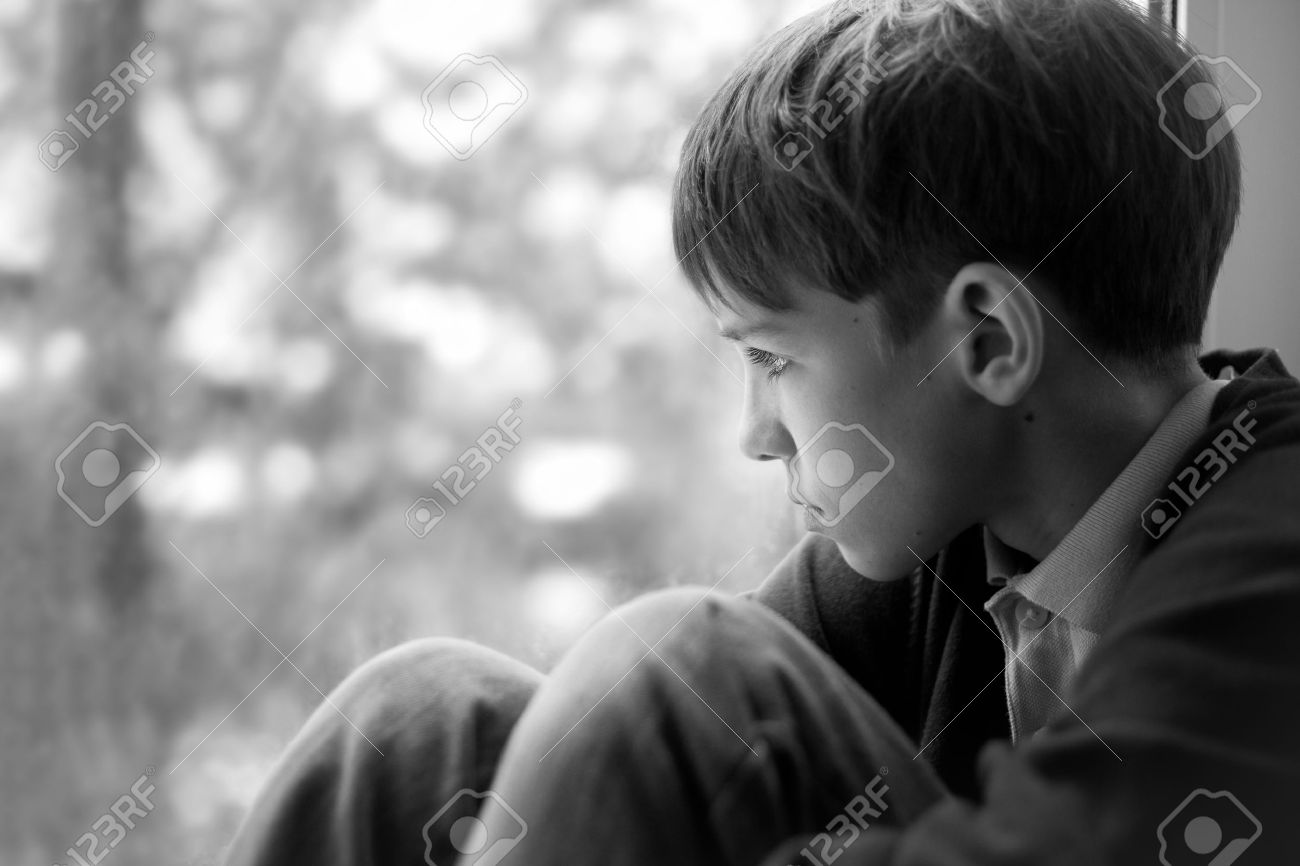 Sad teenager sitting on window black and white photo stock photo 26733510