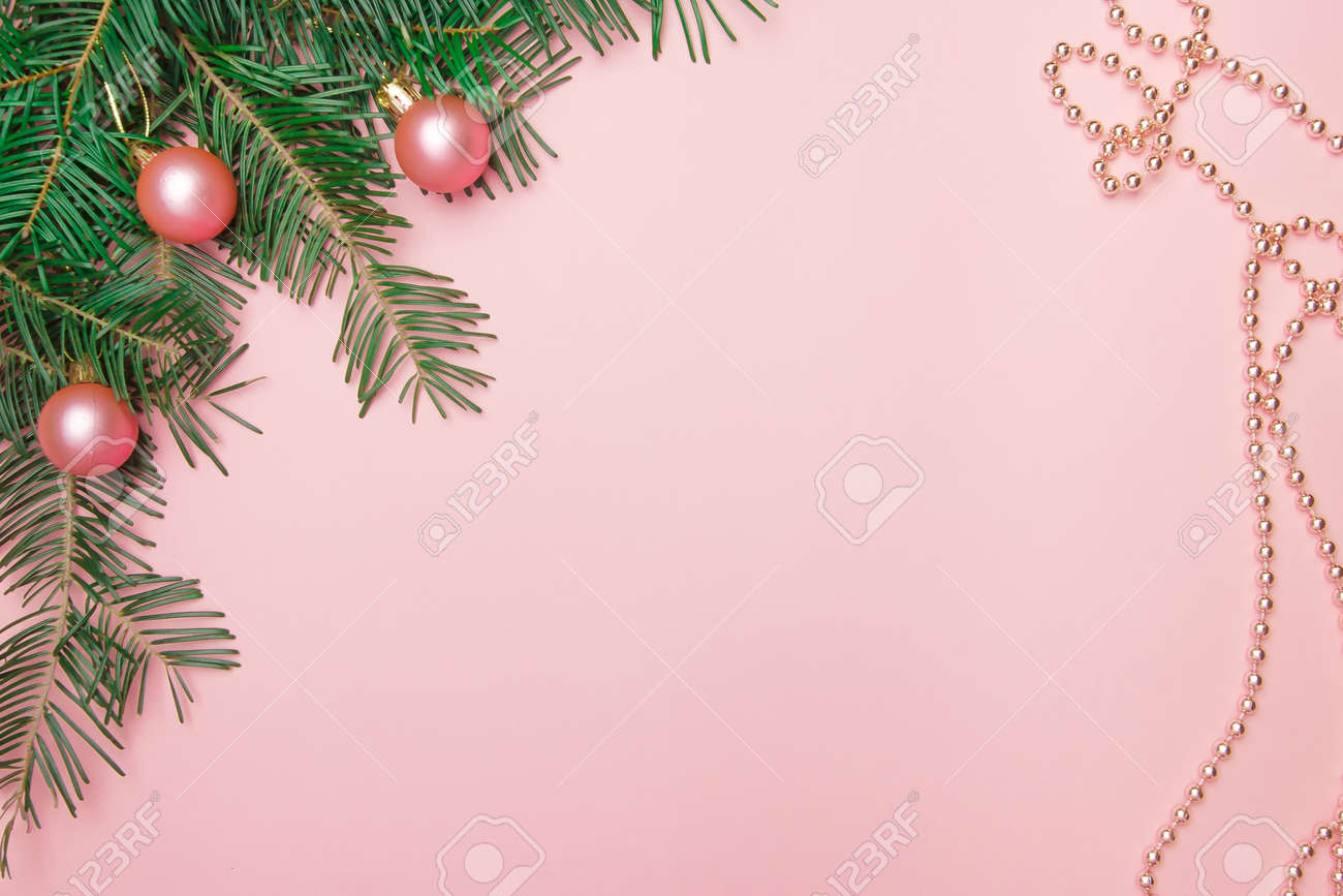 Christmas pink background with fir branch, pink balls and beads in the corner with copy space. - 158155487