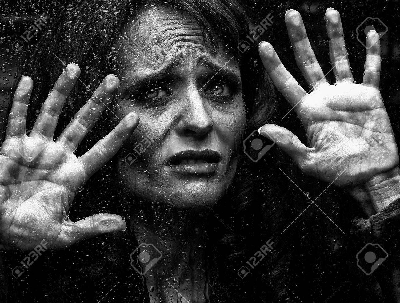 Powerful Portrait Of A Scared Woman Behind Glass Stock Photo