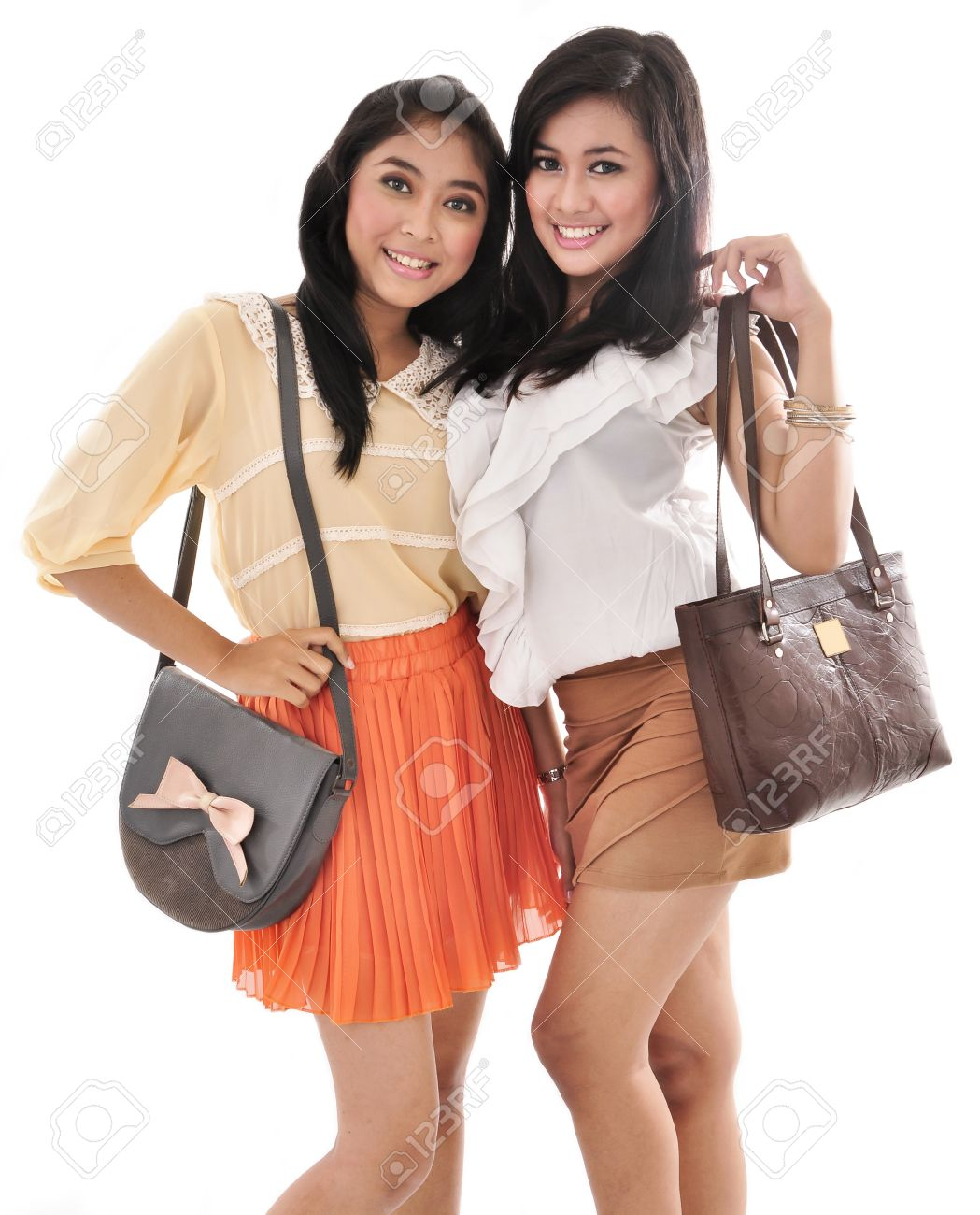 Two Sexy Girls Carrying Bags Isolated On White Background Stock Photo