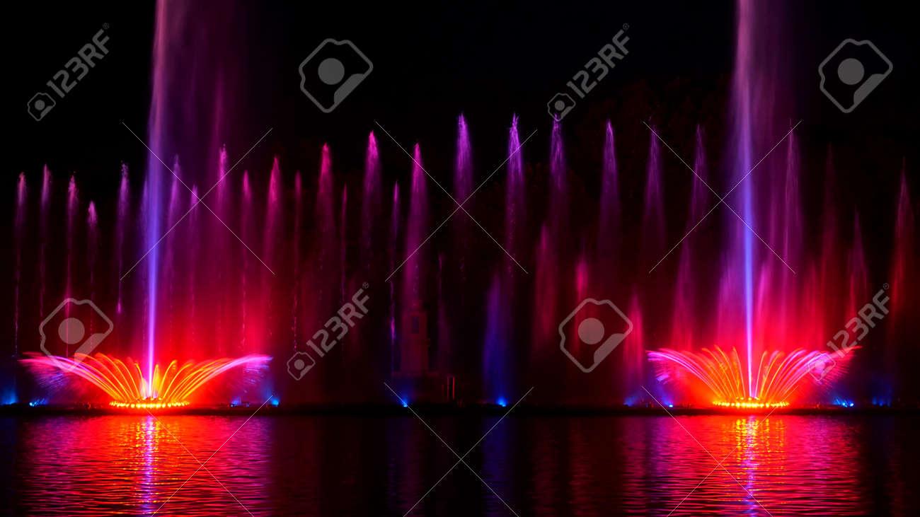 Night laser fountain show, on the Roshen embankment, the Ukrainian city of Vinnitsa.Musical fountain with laser animations.Musical fountain Roshen in Vinnitsa, Ukraine.Evening show Roshen fountain. - 154827561
