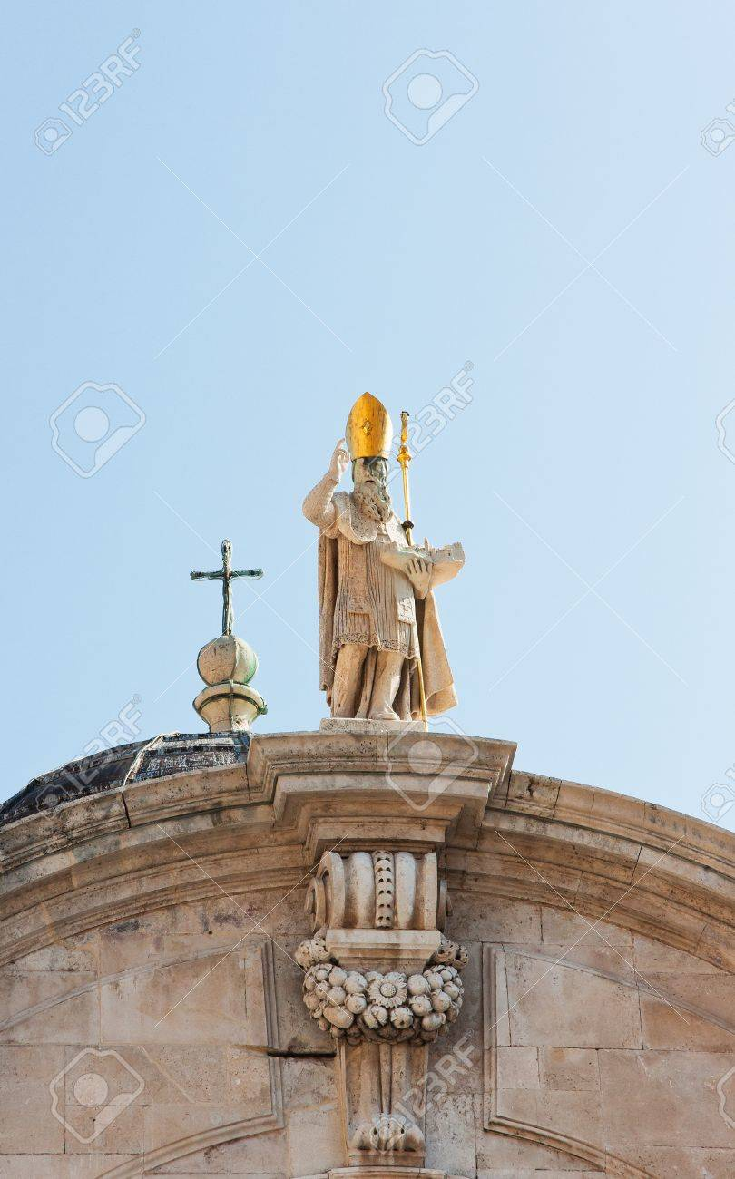 Sculpture Of A Stone Made Holy Man On A Roof With A Tall Golden ...