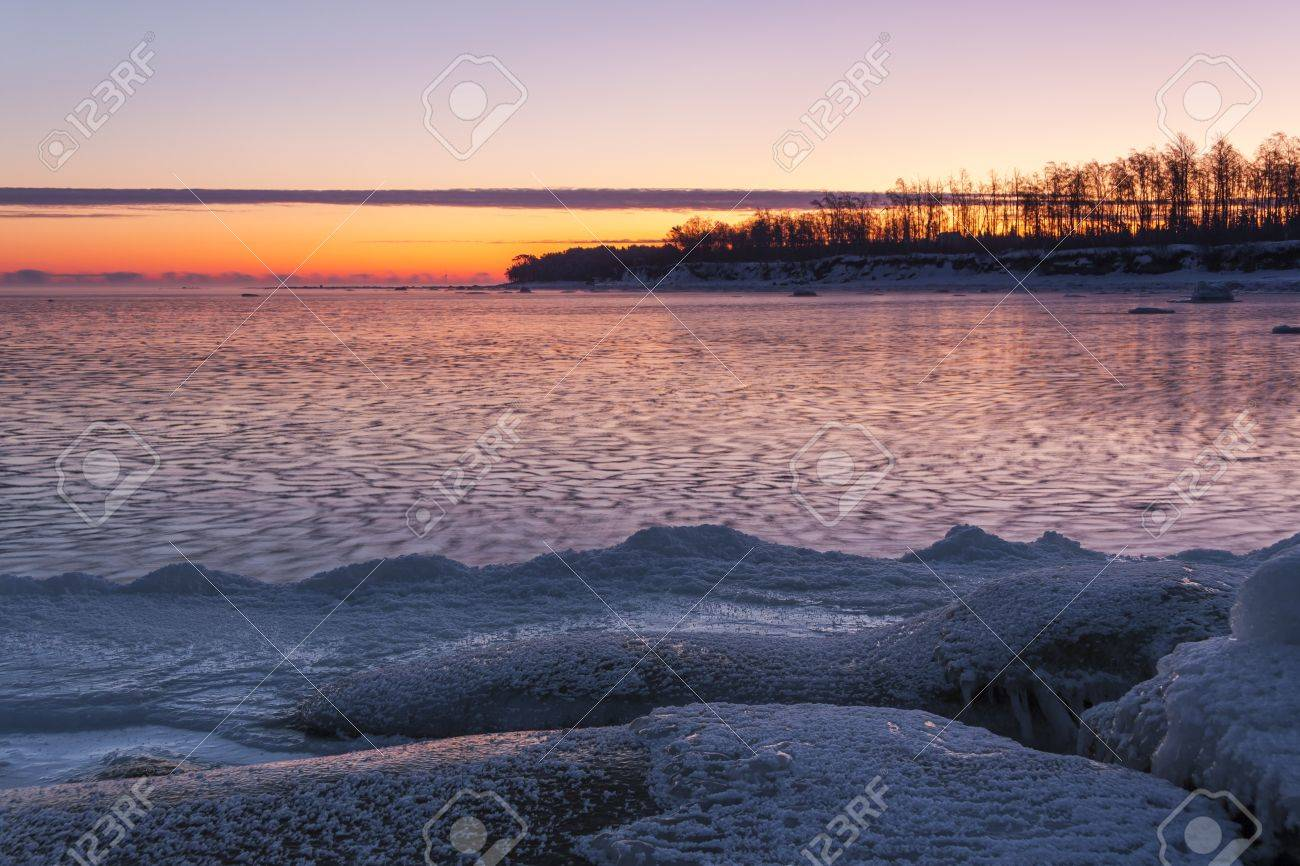Icy sea at sunrise, snowy land in foreground and a piece of land in background Stock Photo - 16101796