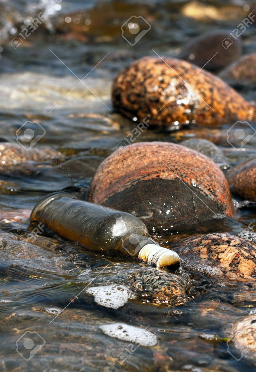 Glass made old alcohol bottle left onto rocks near water Stock Photo - 17963216