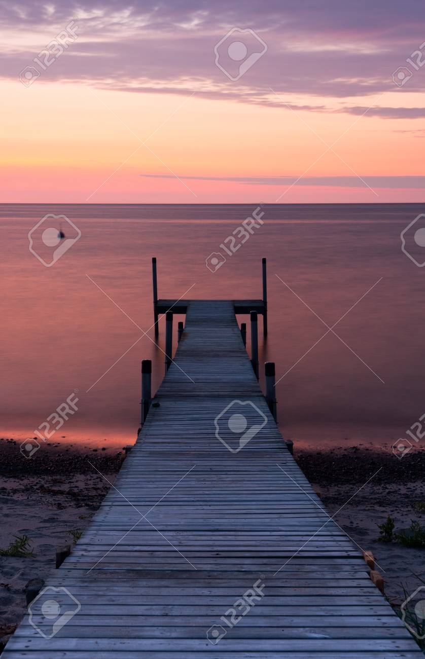 Long wooden bridge leading from ground into the sea at sunset at calm weather Stock Photo - 17963122