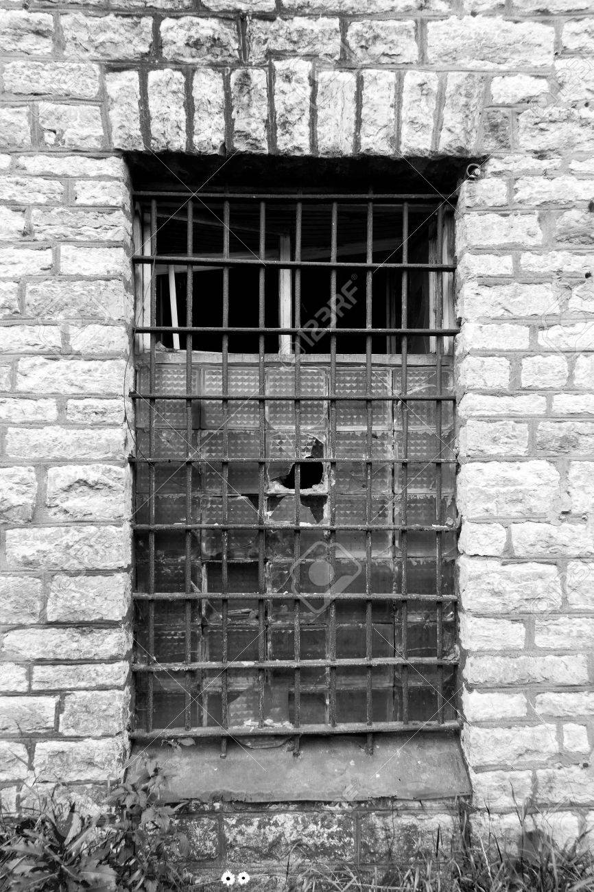 Old grated prison window in limestone wall Stock Photo - 18257336