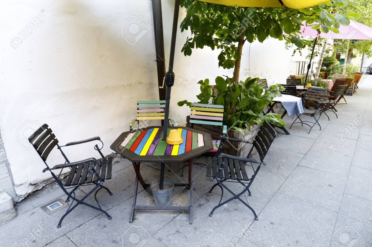 Colorful outdoor cafe tables and chairs near yellow wall stock photo 84185864