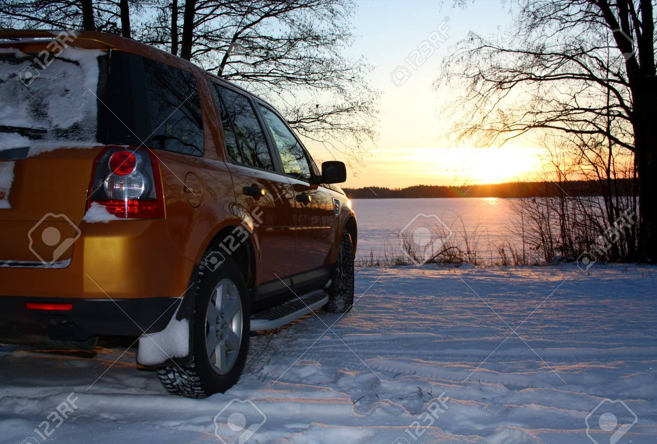Car by frozen lake at sunset - 11581696