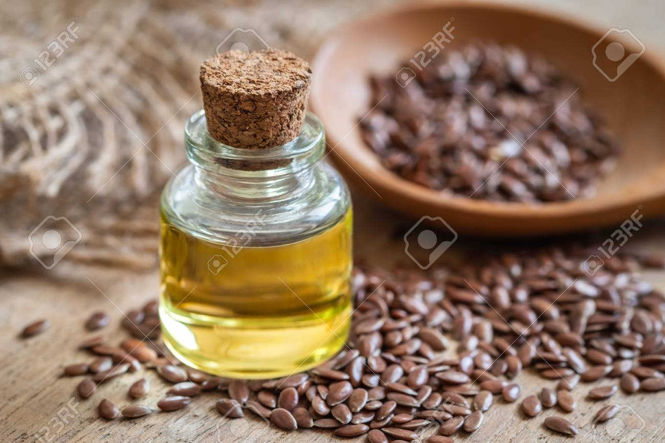 Flaxseed Oil In Bottle And Brown Flax Seeds On Wooden Spoon