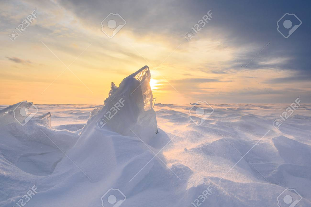 Boundless icy landscape during a snowstorm at sunset in winter. - 65940985