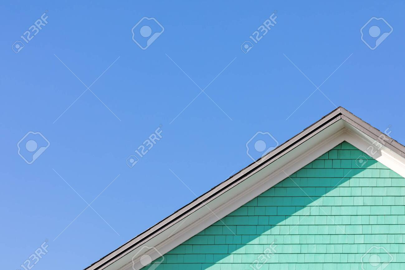 Colourful rooftop and blue sky. The traditional houses of the Magdalen Islands, Canada.Peppermint green, blue and white composition with space for text. - 140828781