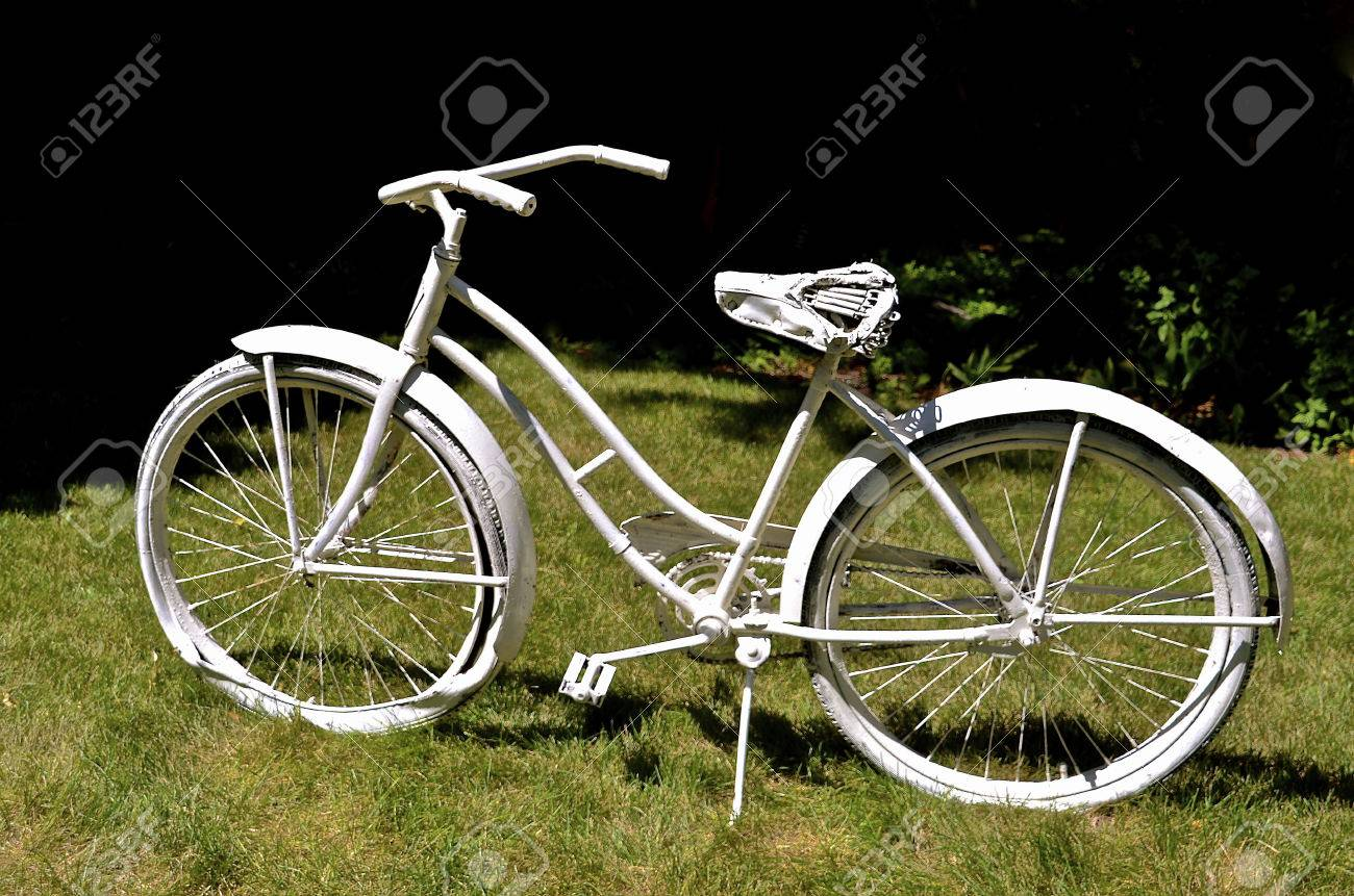 Le vélo de Une vieille fille junker a été peint en blanc et est utilisé  comme une cour ou un jardin décoration