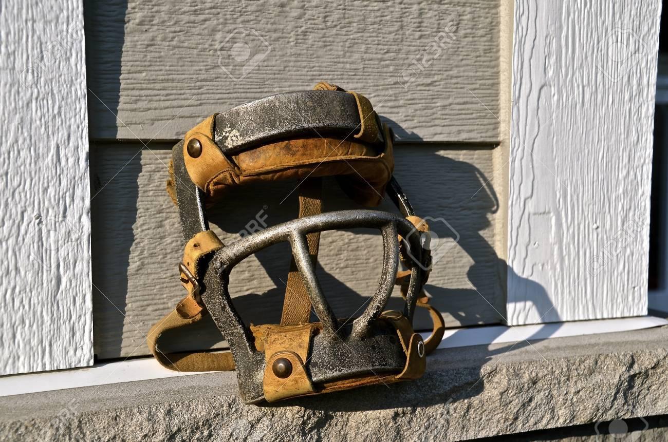 eine alte metall-baseballmaske für einen fänger ruht auf einem