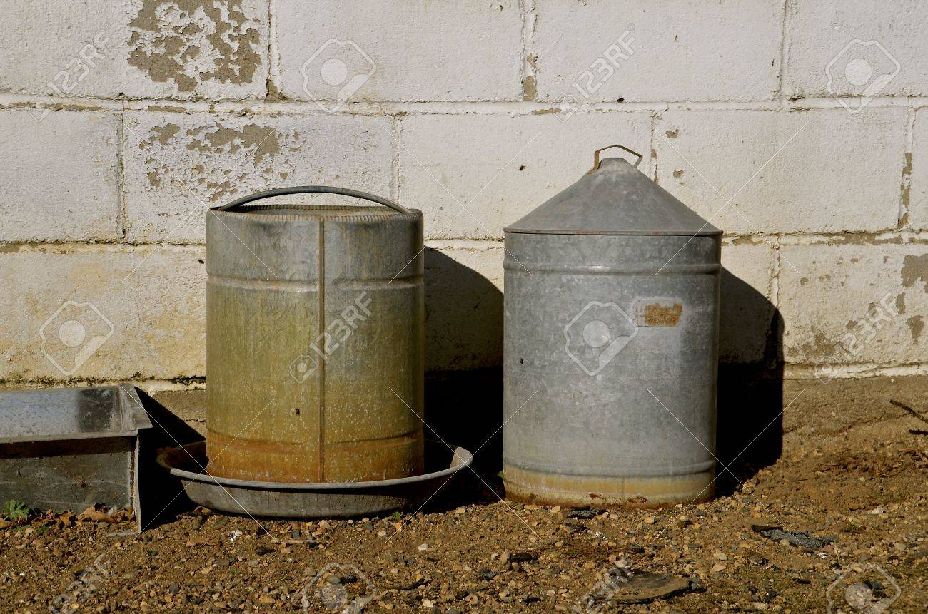 Old Metal Chicken Feeder And Water Container In Front Of A Block Henhouse  Stock Photo