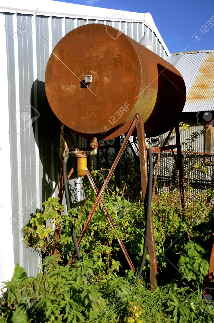 An old rusty fuel tank is perched on a stand alongside a steel