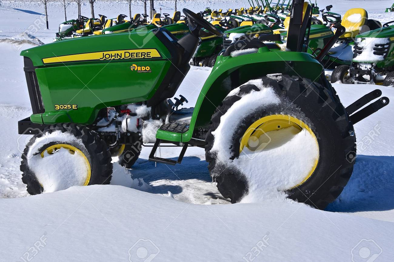 MOORHEAD, MINNESOTA, March 5, 2018 : The 3025E John Deere tractor covered with snow is a product of John Deere Co, an American corporation that manufactures agricultural, construction, forestry machinery, and diesel engines. April 8, 2017: The 3025E J - 97342118