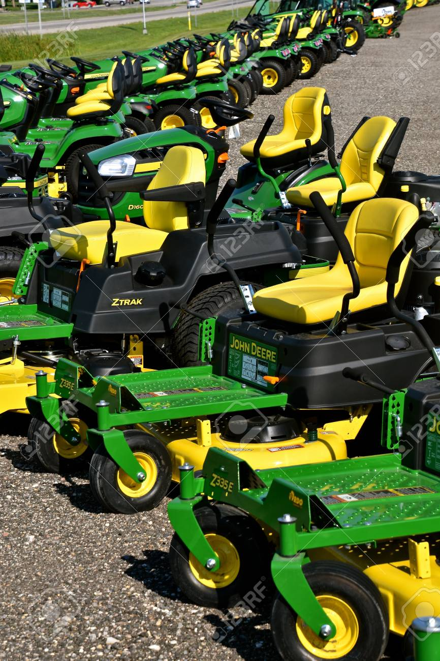 HAWLEY, MINNESOTA, August 22, 2017: A row of green and yellow new riding lawn mower tractors are products of John Deere Co, an American corporation that manufactures agricultural, construction, forestry machinery, diesel engines, and drive trains - 100006055