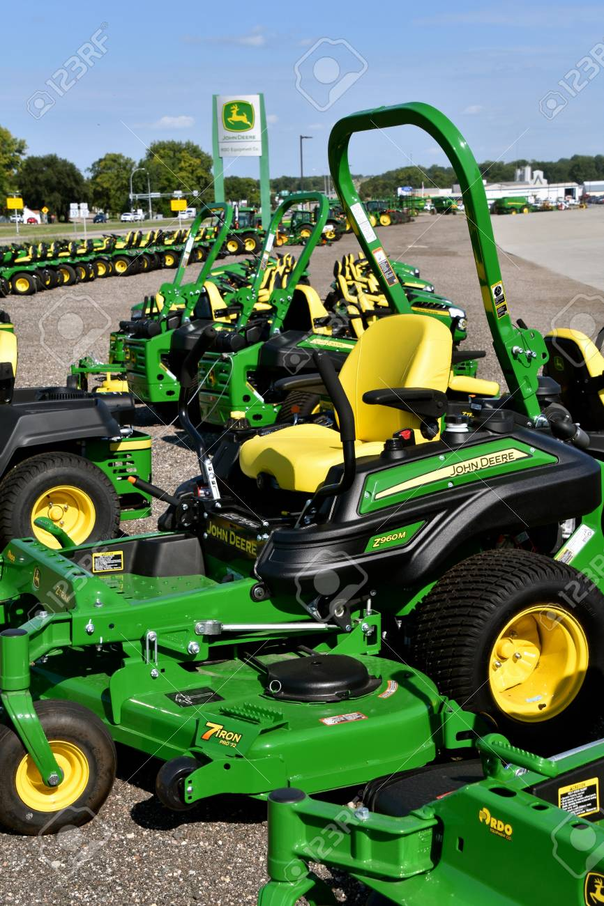 HAWLEY, MINNESOTA, August 22, 2017: A row of green and yellow new riding lawn mower tractors are products of John Deere Co, an American corporation that manufactures agricultural, construction, forestry machinery, diesel engines, and drive trains - 100091034