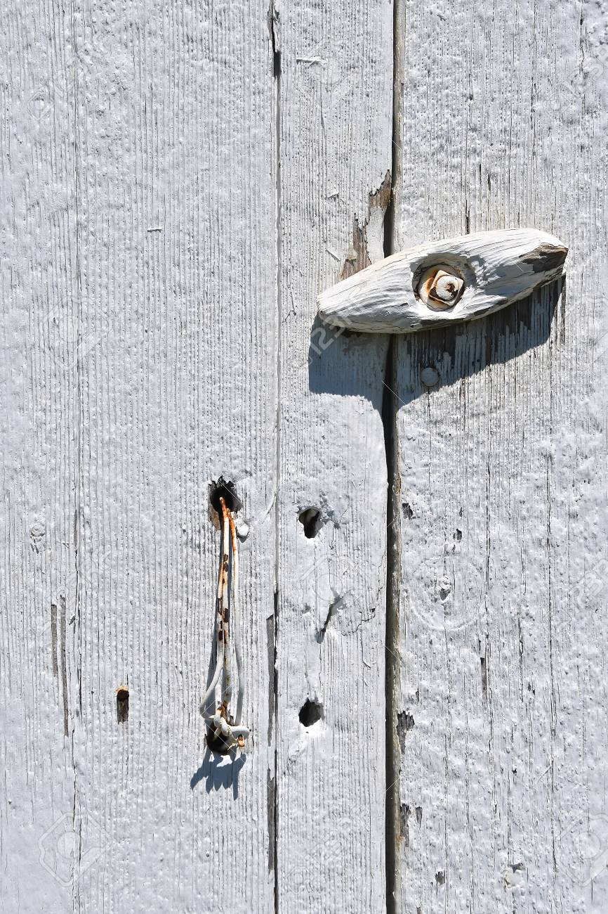 An Old Whitewashed Shed Door With A Wire Latch And Door Knob Stock Photo    102836428