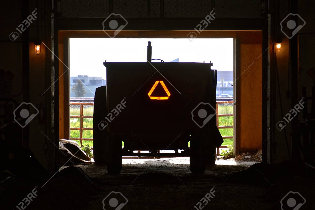 A feed cart backed into a shed displays the Slow Moving Vehicle sign. - 105950732