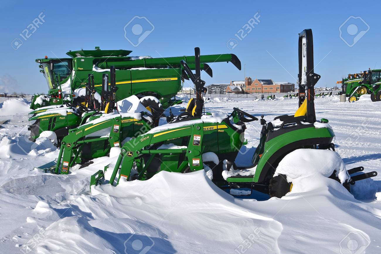 MOORHEAD, MINNESOTA, February 14, 2109: The row of new 220R snow lawn mowers covered are products of John Deere Co, an American corporation that manufactures agricultural, construction, forestry machinery, diesel engines, and drivetrains. - 117735597