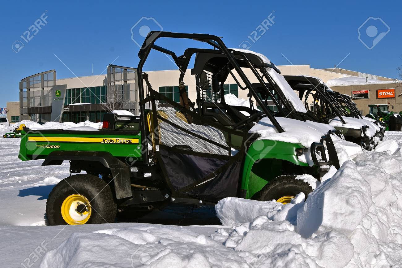 MOORHEAD, MINNESOTA, February 14, 2109: The row of snow covered Gators are products of John Deere Co, an American corporation that manufactures agricultural, construction, forestry machinery, diesel engines, and drivetrains. - 117735600