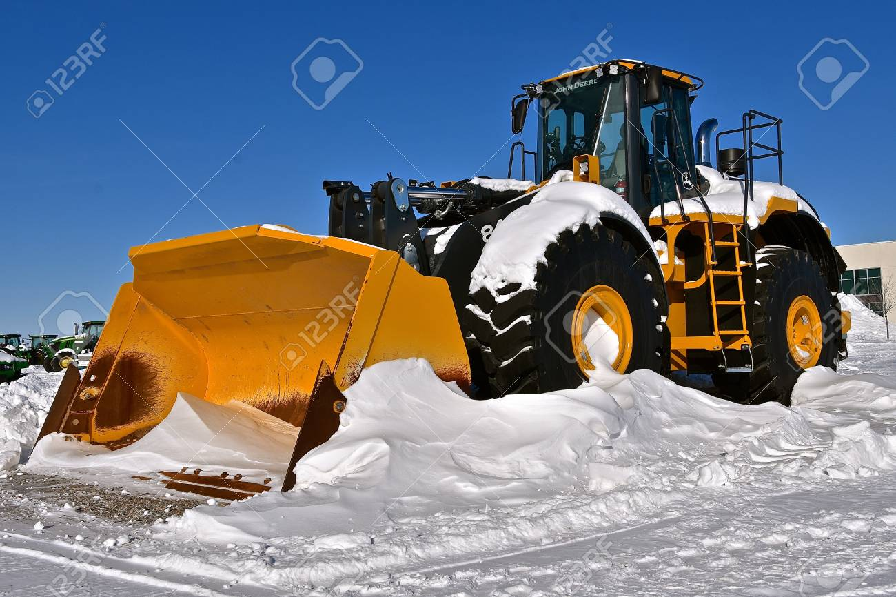 MOORHEAD, MINNESOTA, February 14, 2019: A huge 4-wheel drive tractor with a massive bucket for snow removal tractor is a product of John Deere Co, an American corporation that manufactures agricultural, construction, forestry machinery, diesel engines, a - 117735602