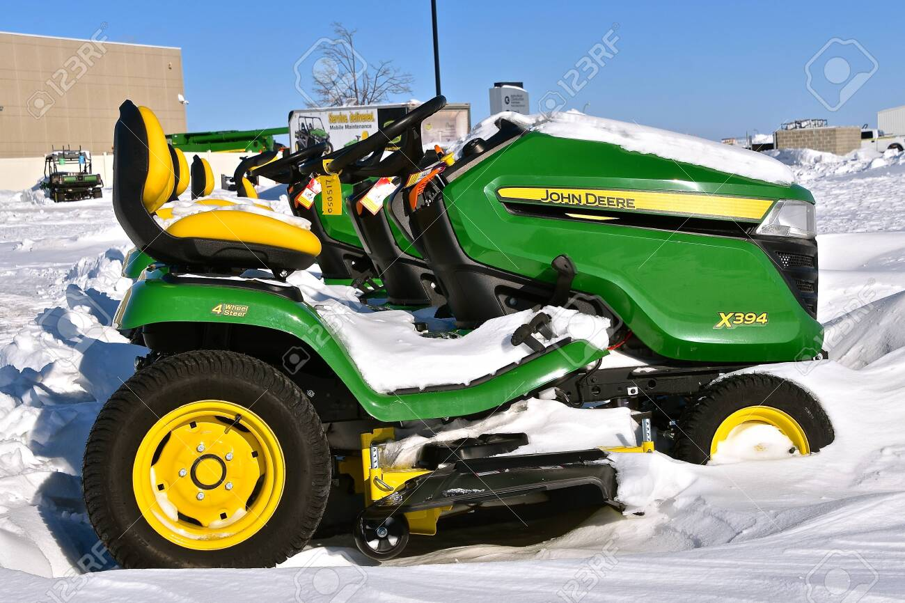 MOORHEAD, MINNESOTA, February 14, 2019: The snow covered X394 riding lawn mower is a product of John Deere Co, an American corporation that manufactures agricultural, - 117735603