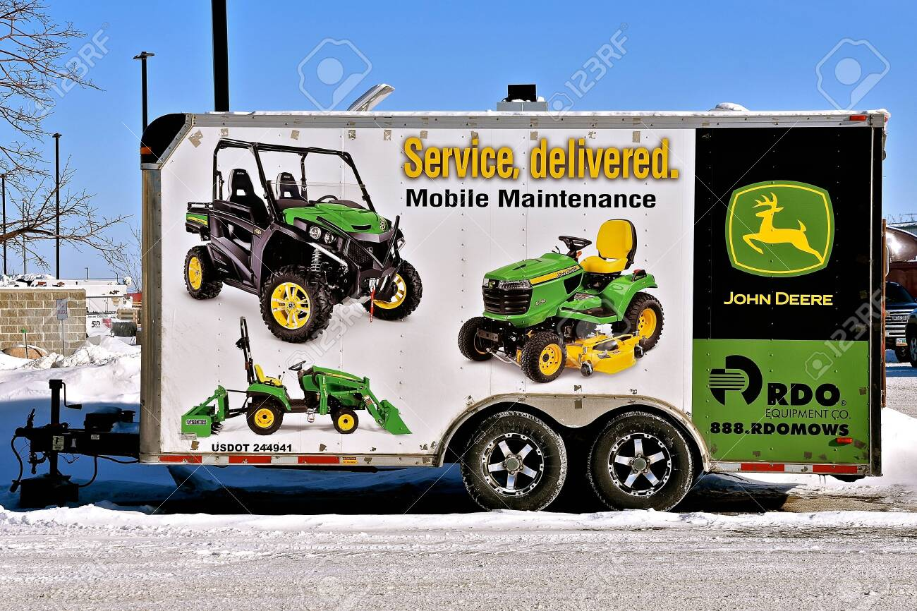 MOORHEAD, MINNESOTA, February 14, 2019: The double axle 4 wheeled trailed is used to haul products of John Deere Co, an American corporation that manufactures agricultural, - 117735604