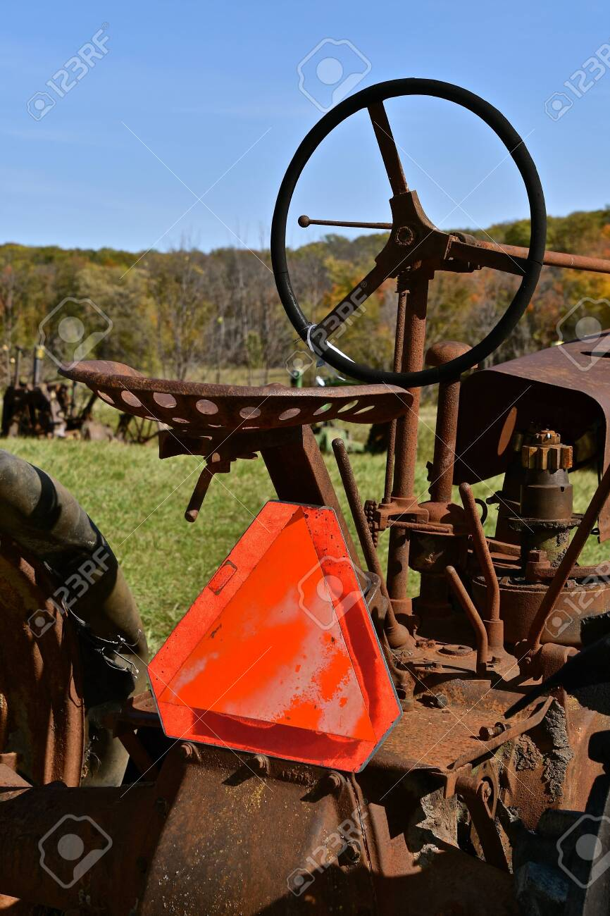 An old rusty tractor has an attached Slow Moving Vehicle Sign providing safety. - 139284896