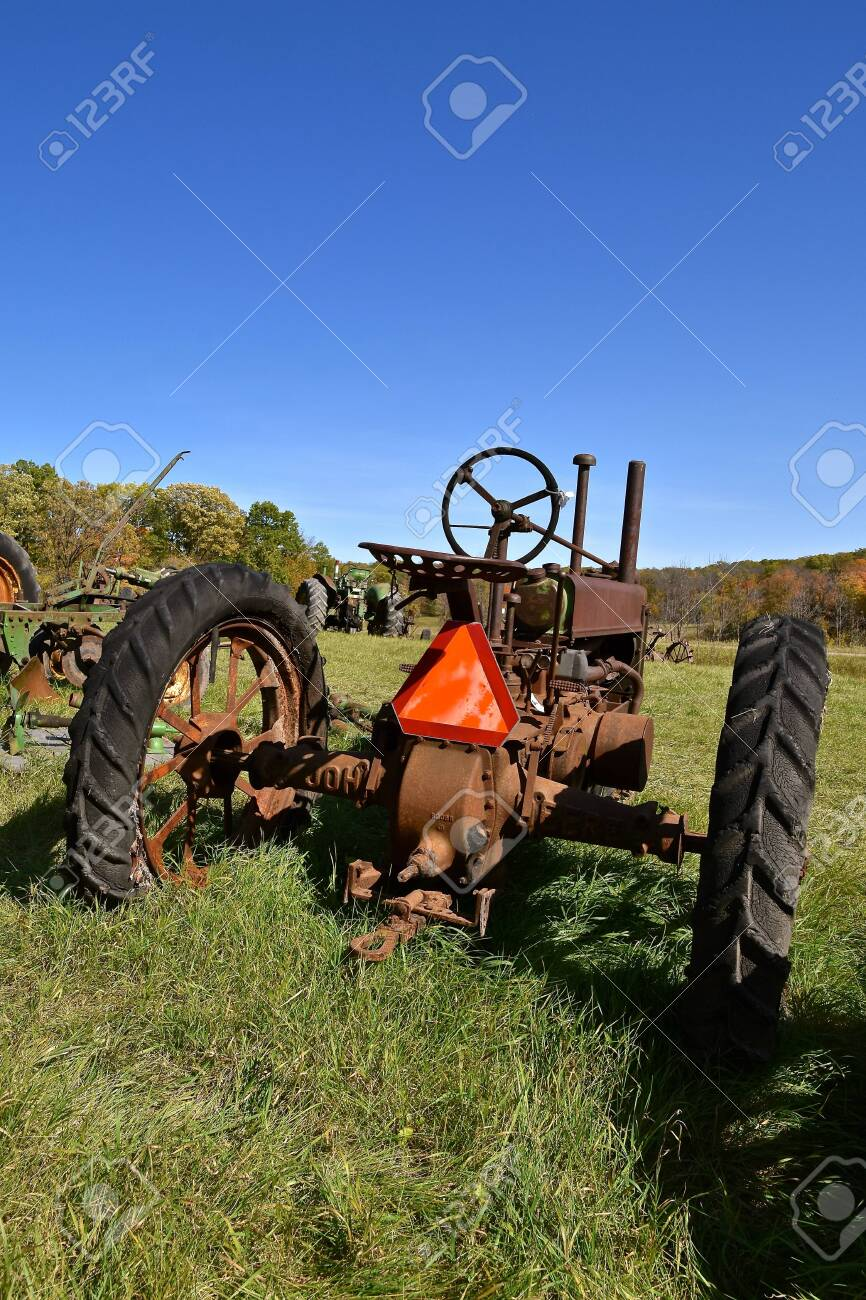 VERGAS, MINNESOTA, October 6, 2019: The parked old tractor with a SMV orange sign is a product of John Deere Co, an American corporation that manufactures agricultural and construction equipment. - 138511269