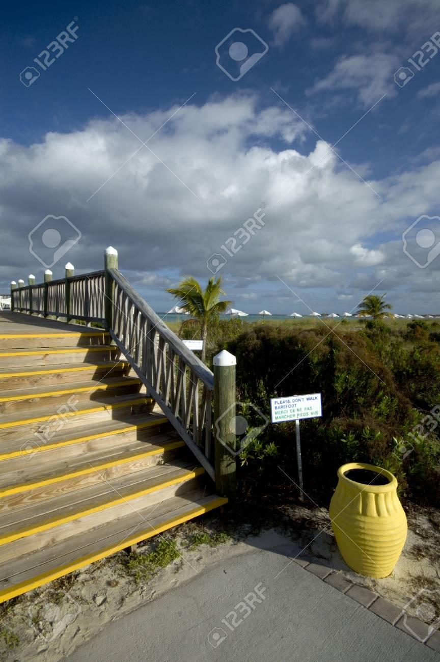 don't walk barefoot sign  boardwalk yellow urn by the beach caribbean sea Stock Photo - 735723