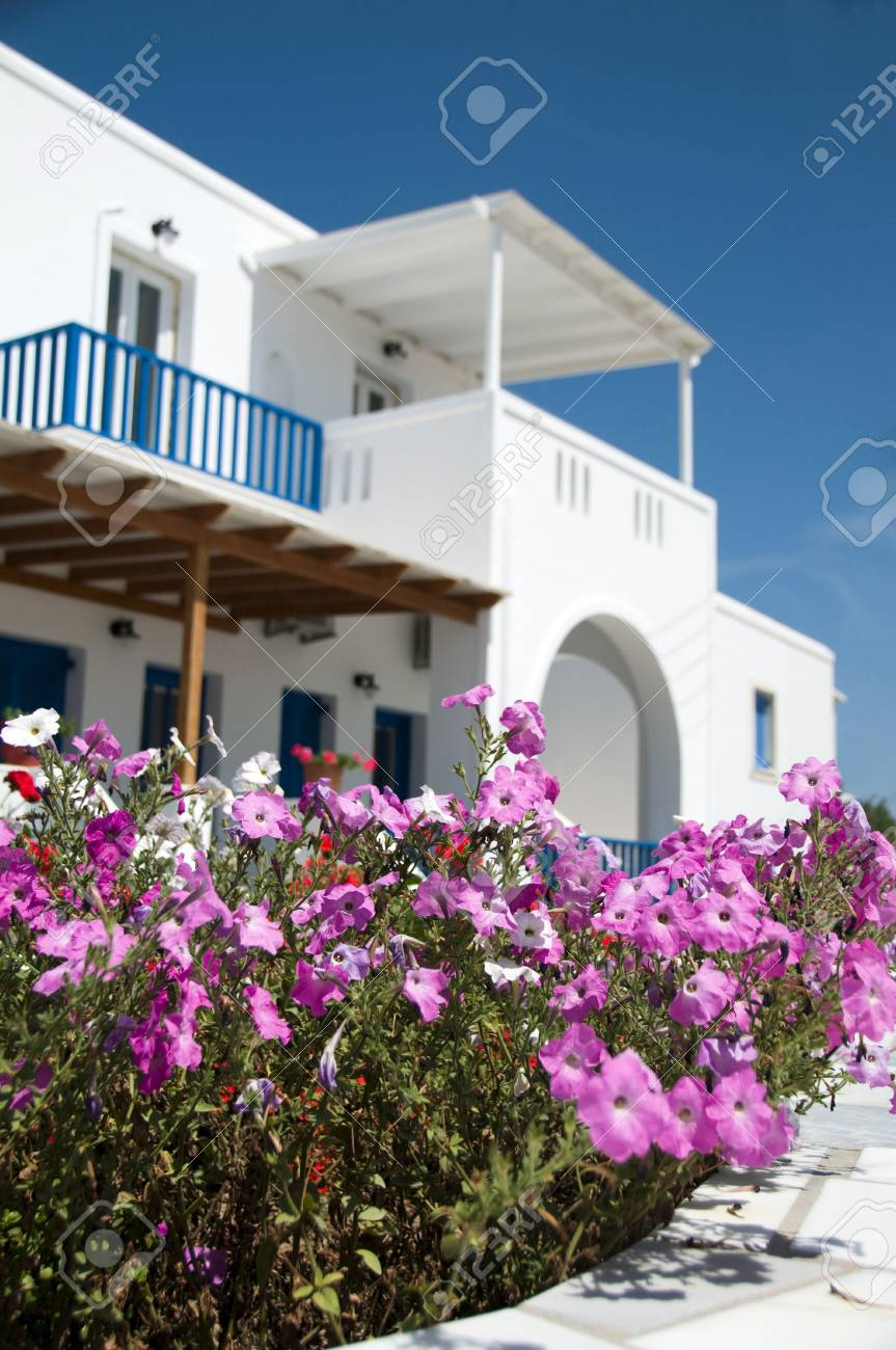 whitewashed architecture with arches and blue shutters and rails common to the greek cyclades island with shallow depth of field focus flowers Stock Photo - 4989313