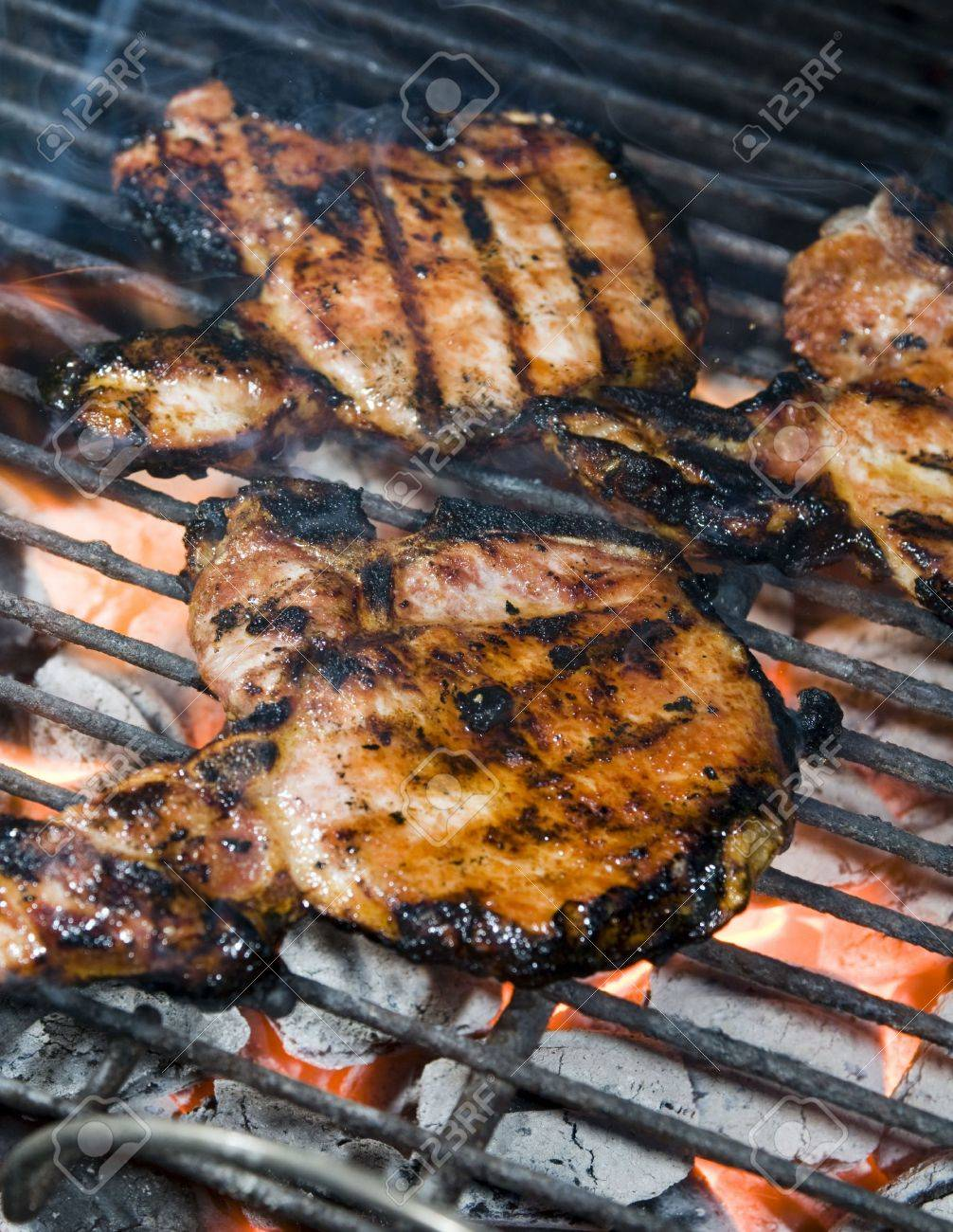 Thin Center Cut Bone In Pork Chops Cooking On A Charcoal Barbecue Grill With Grill Marks