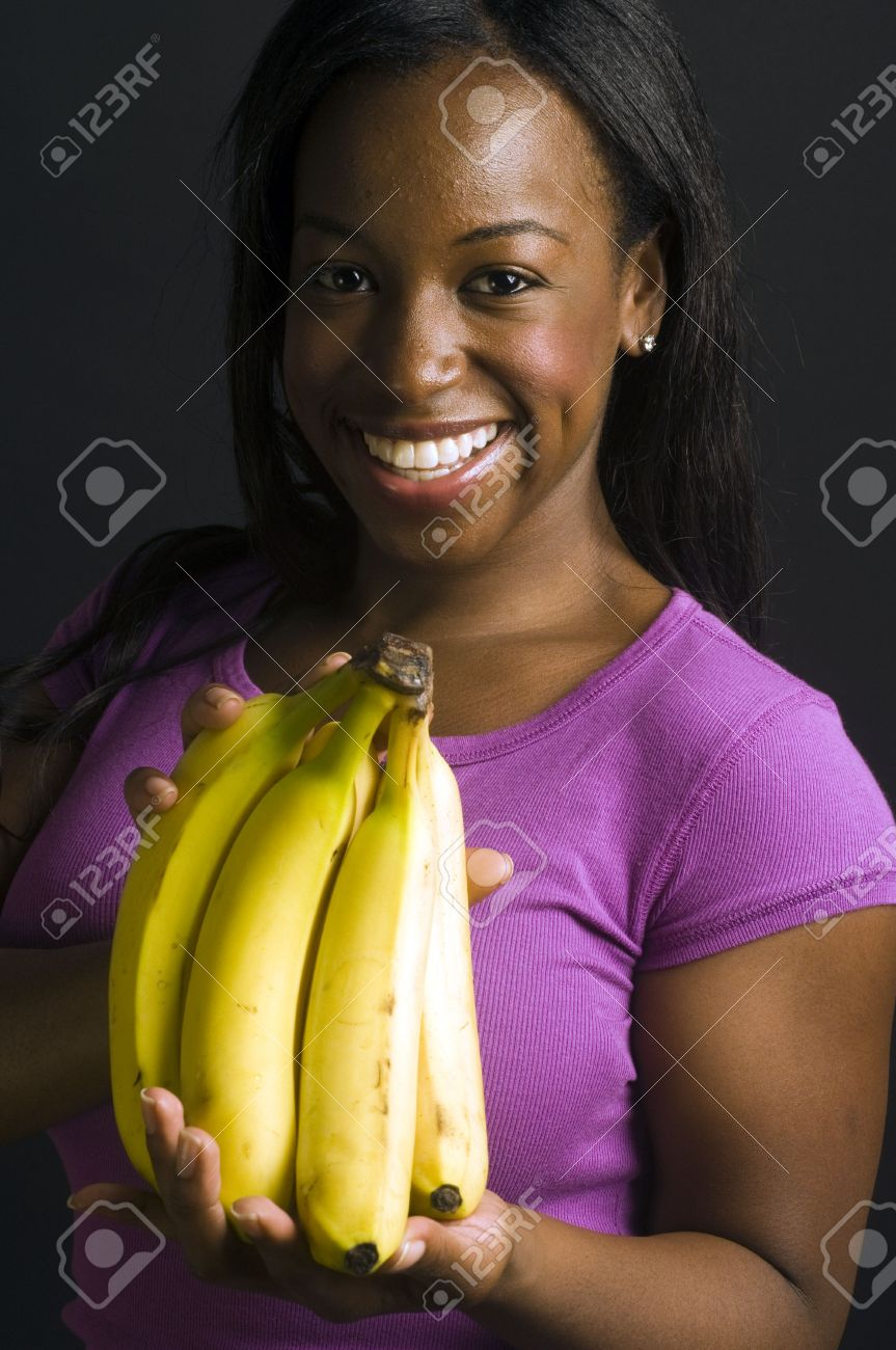 portrait of smiling happy pretty sexy young latin puerto rican black woman  with fresh fruit bananas