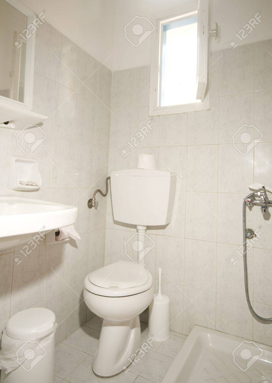 Typical Compact All In One Bathroom With No Shower Curtain And Garbage Bin  For Toilet Paper